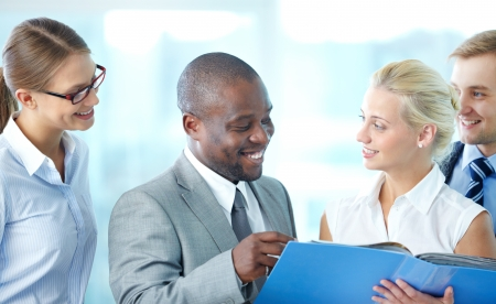 4 people: Portrait of confident employees discussing document at meeting