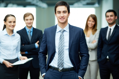 competitive business: Group of friendly businesspeople with male leader in front