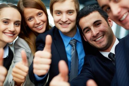 companionship: Retrato de cinco socios de trabajo, manteniendo los pulgares hacia arriba y mirando a la cámara con sonrisas