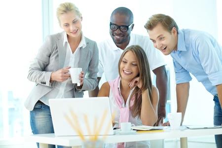 Grupo de estudiantes amistosos o empresarios se reunieron delante del ordenador portátil