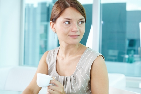 Portrait of a woman holding a white porcelain cup and looking aside photo