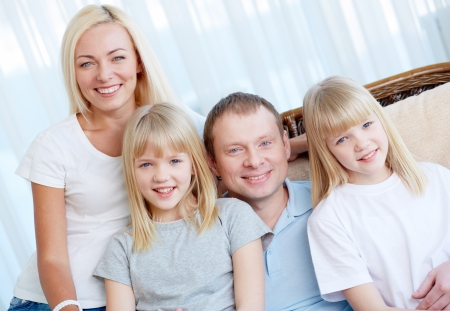 Portrait of happy couple with twin daughters looking at camera with smiles Stock Photo - 17785980