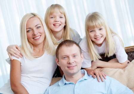 twin sister: Portrait of happy couple with twin daughters resting at home