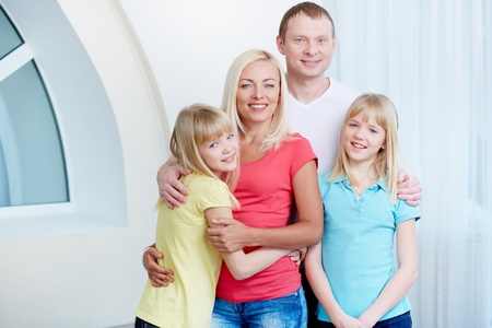 Portrait of happy couple with twin daughters looking at camera at home Stock Photo - 17785878