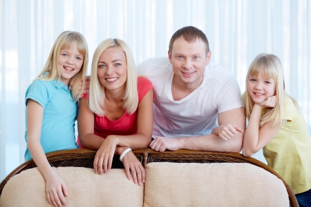 Portrait of happy couple with twin daughters looking at camera at home Stock Photo - 17785838