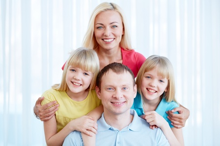 twin sister: Portrait of happy family of four looking at camera at home