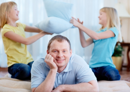 Portrait of happy man looking at camera with his daughters having fun on background photo