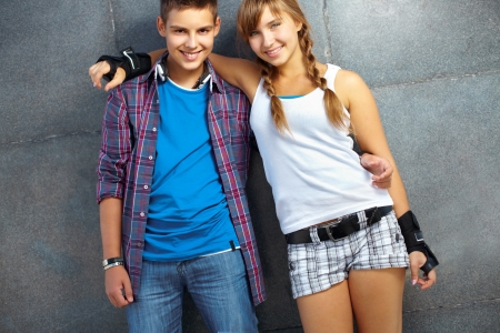 youthful: Couple of happy teens looking at camera outside