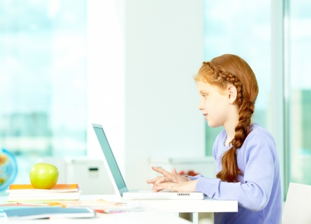elementary students: Portrait of smart schoolgirl sitting in classroom and typing