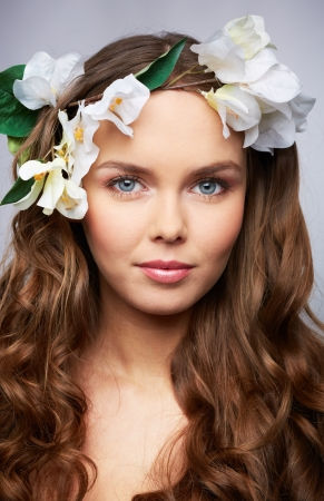 beauty shot: Vertical portrait of a beautiful young woman with a flower in her hair