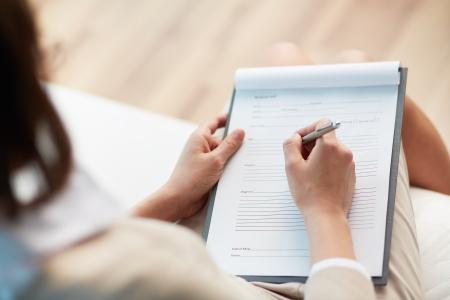 terapia psicologica: Consejero Mujer escribiendo una cierta información sobre su paciente