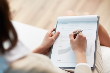 questionnaires: Female counselor writing down some information about her patient