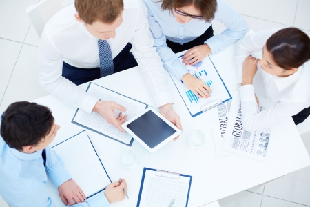 Group of business partners interacting while planning work at meeting photo