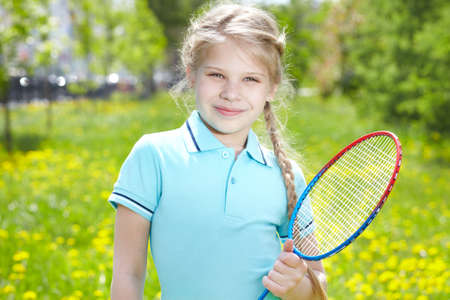 Portrait of little girl with tennis racket looking at camera photo