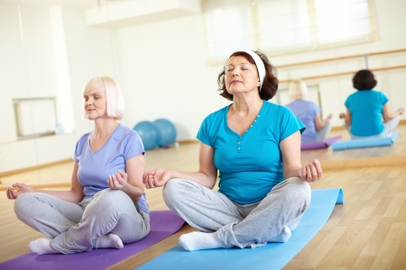 practicing: Portrait of two aged females doing yoga exercise in sport gym