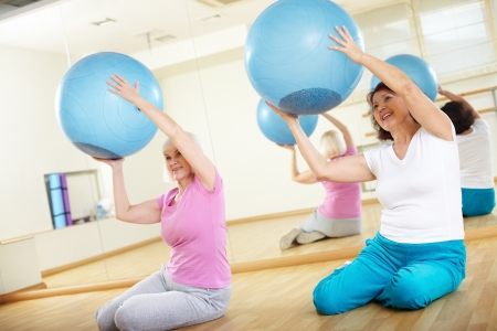 Portrait of sporty females doing physical exercise with fitness balls in sport gym  photo