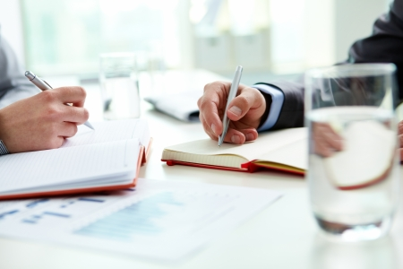 corporate training: Image of male and female hands with pens over open notebooks at seminar