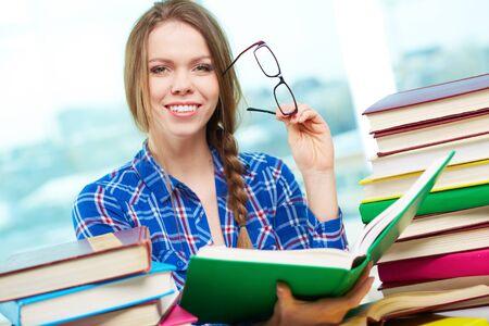 diligente: Retrato de estudiante diligente mirando a la c�mara con el libro abierto en las manos