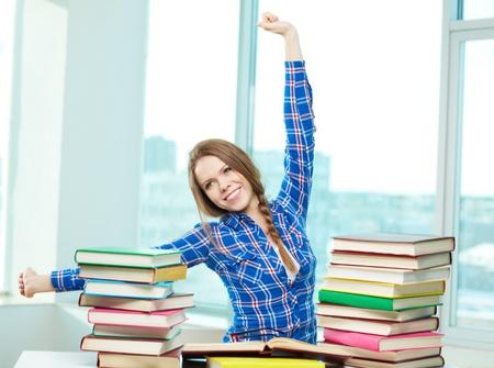 diligente: Retrato de estudiante diligente relajarse durante los estudios con estanter�as de libros en el frente