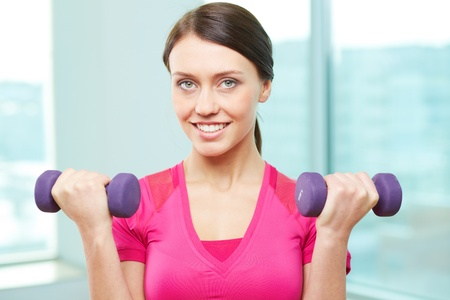 Portrait of pretty girl with dumbbells looking at camera in gym Stock Photo - 17883998