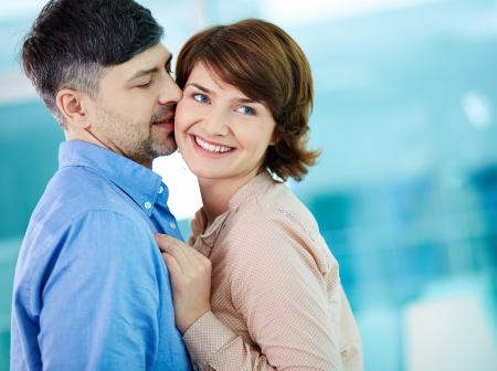 mid adult man: Portrait of happy middle aged woman enjoying her husband kiss Stock Photo