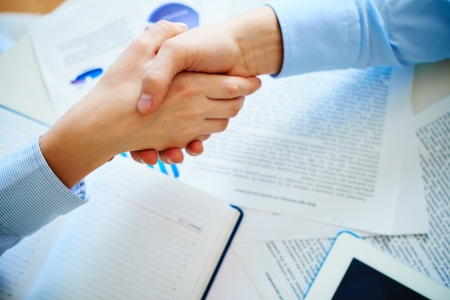 handshaking: Close-up of female and male handshaking over workplace with business documents