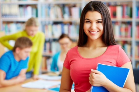 college student: Portrait of pretty girl looking at camera in college library with her group mates on background
