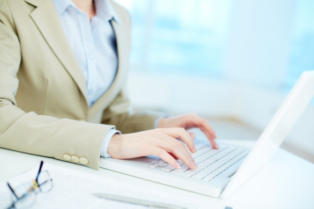 computer user: Close-up of white collar worker typing on laptop Stock Photo