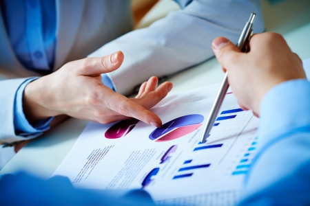 financial executive: Close-up of female and male hands pointing at business document while discussing it Stock Photo