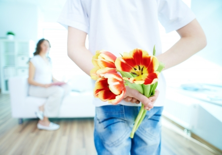 gift behind back: Rear view of lad with bunch of beautiful tulips behind back preparing nice surprise for his mother