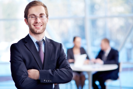team leader: Male leader looking at camera with his partners working on background Stock Photo
