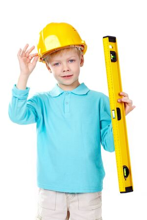 Cute boy in hardhat holding a level and looking at camera photo