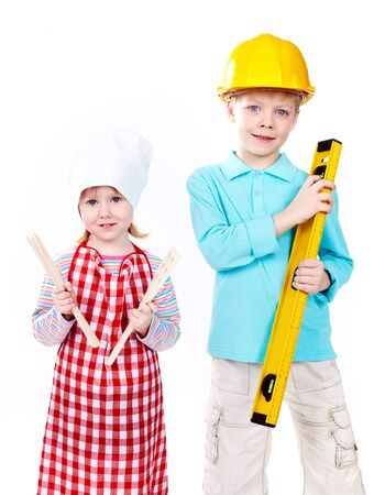 Cute boy in hardhat with level and little girl in apron with kitchen tools looking at camera photo