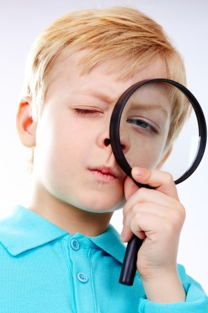 blue eyed: Portrait of a kid looking through magnifying glass Stock Photo