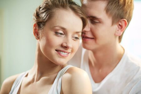 cuddled: Portrait of smiling young woman being cuddled by loving man