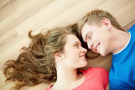 jovenes enamorados: Por encima del ángulo de la joven pareja feliz mirando el uno al otro mientras está acostado en el suelo
