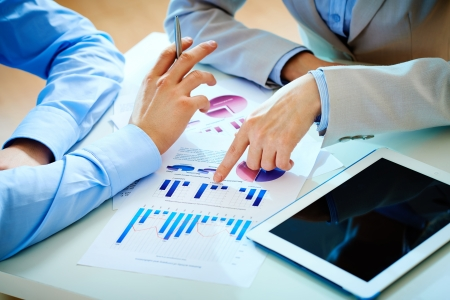 business review: Close-up of female hand pointing at business document while explaining chart