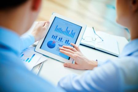 datos personales: Primer plano de socios de negocios que buscan en documento empresarial en touchpad Foto de archivo
