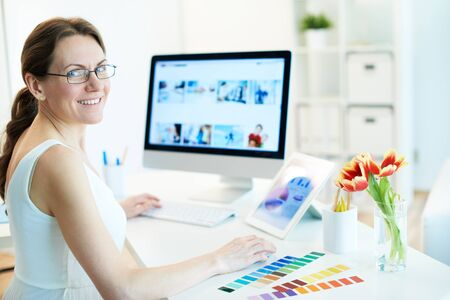 nice looking: Portrait of happy female designer working and looking at camera