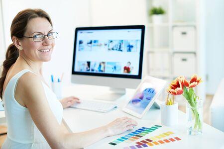 mujeres sentadas: Retrato del diseñador femenino feliz trabajando y mirando a la cámara