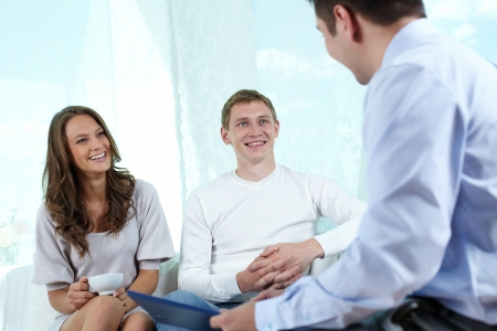 financial adviser: Insurance consultant or financial adviser having a friendly talk with a young couple