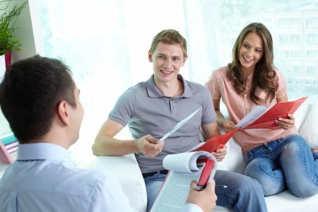 rentable: Manager y sus clientes alegres discutir el programa de seguro m�s rentable para una familia joven Foto de archivo
