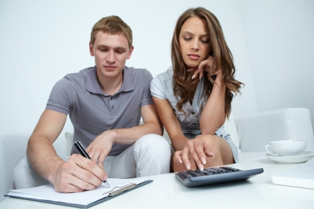 budget crisis: Young couple coming across some imbalance while planning their family budget