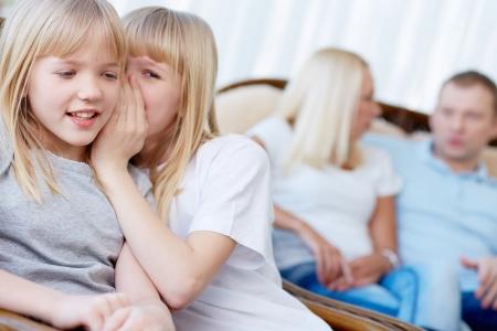 niñas gemelas: Retrato de niña dulce con expresión pensativa con la hermana gemela susurra algo a su alrededor por