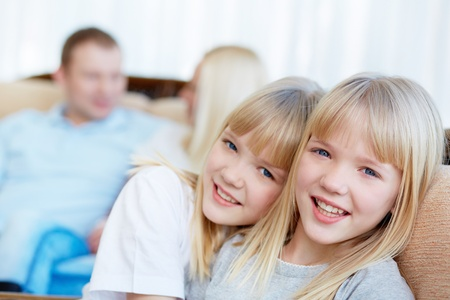 Portrait of happy twin girls looking at camera with their parents behind Stock Photo