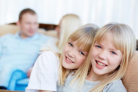 niñas gemelas: Retrato de dos niñas felices mirando a la cámara con sus padres detrás