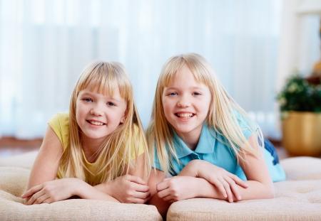 niñas gemelas: Retrato de gemelos felices mirando la cámara en casa