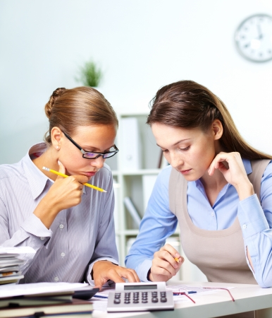 Portrait of two businesswomen working with papers in office photo