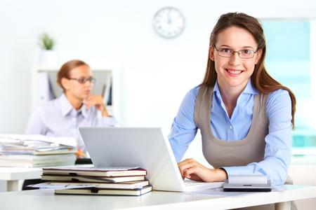 computer user: Portrait of pretty secretary using laptop in office