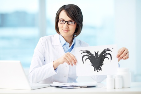 clinical psychology: Smiling psychologist showing paper with Rorschach inkblot